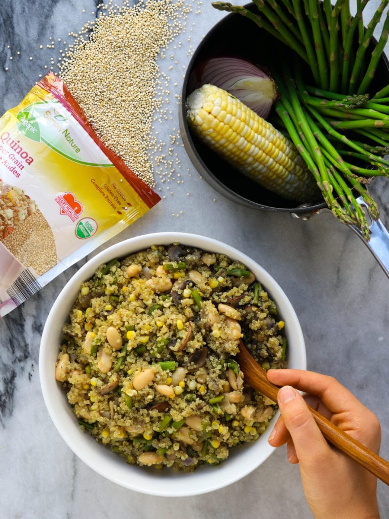 pot filled with corn, red onion and asparagus next to packageof quinoa and white bowl filled with cooked quinoa