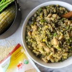 white bowl filled with asparagus mushroom quinoa and wooden serving spoon