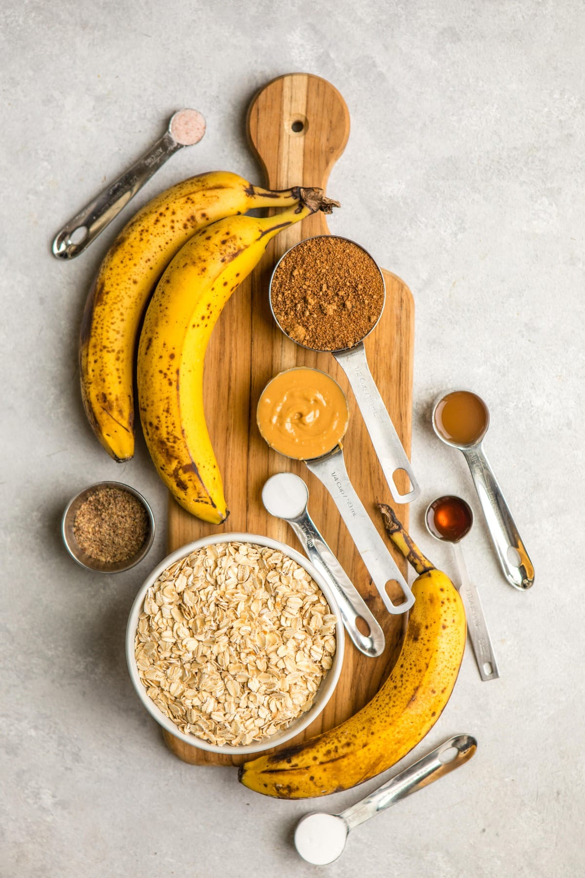 ingredients for banana bread in measuring cups on long wooden serving board
