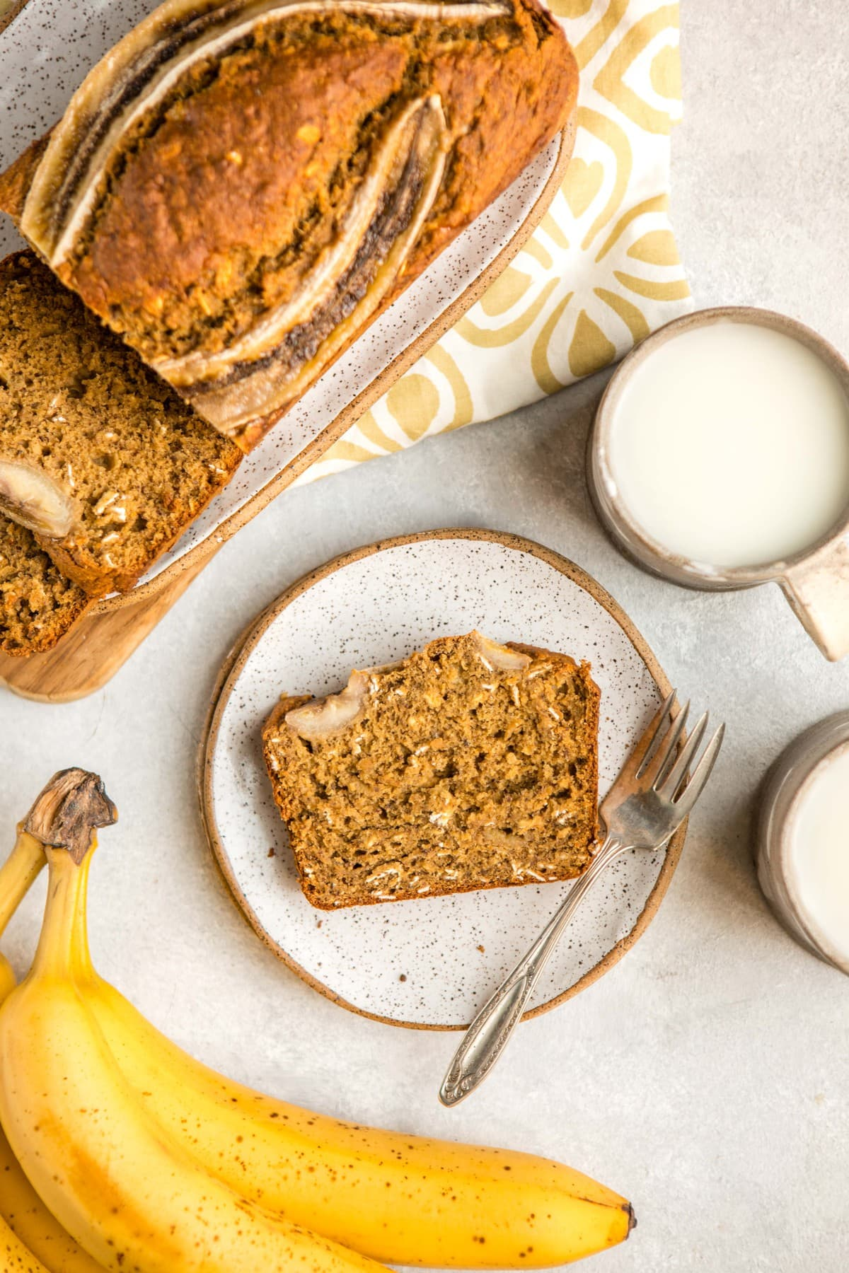slice of vegan banana bread on small white plate next to loaf on white serving platter