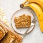 slice of vegan banana bread on white speckled plate on light gray background