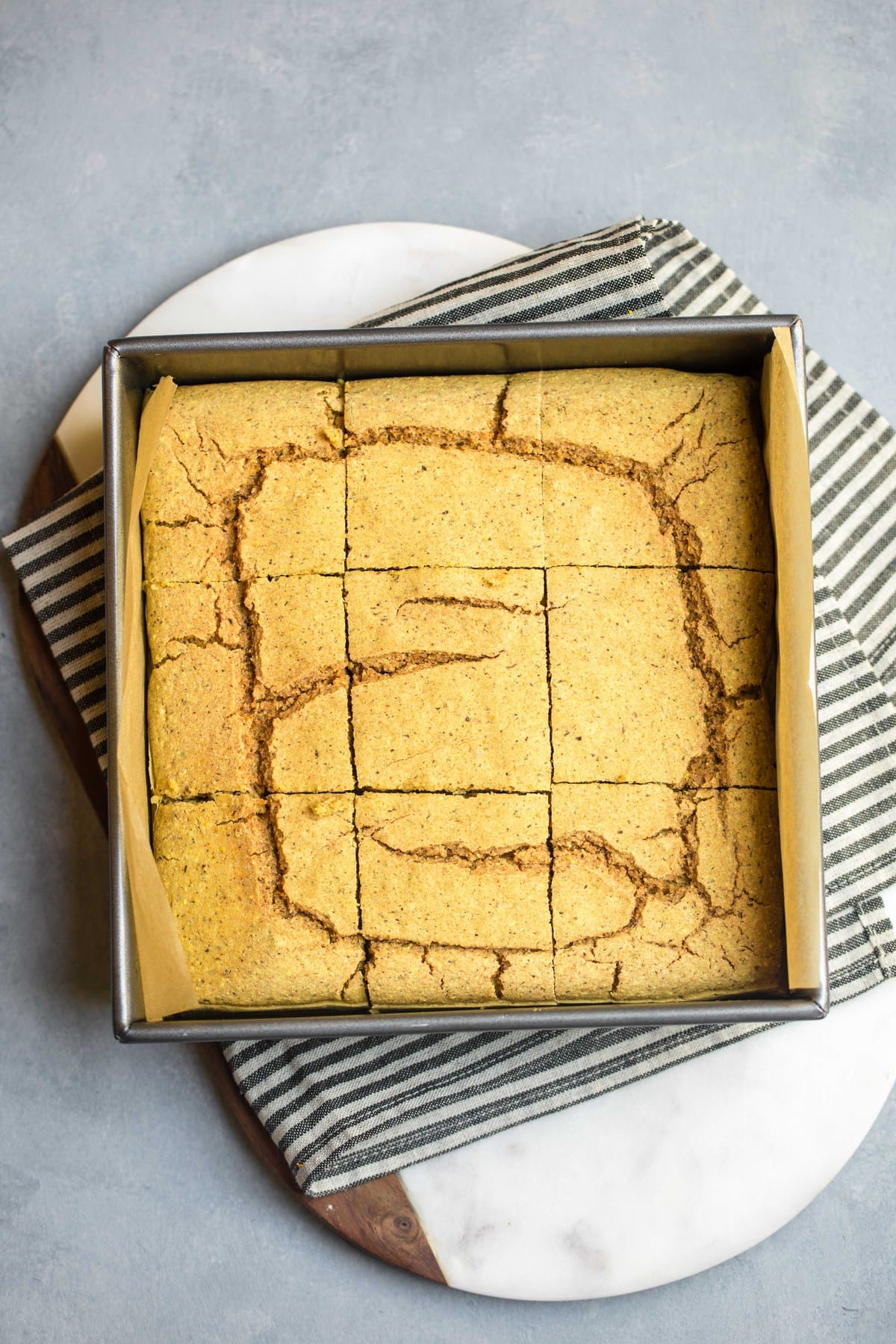 baked and sliced vegan cornbread in square baking tin on white cutting board