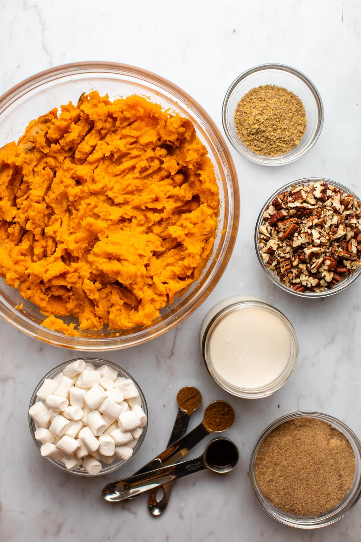 ingredients for sweet potato casserole in small glass bowls on marble background