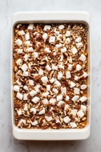 sweet potato casserole topped with marshmallows and pecans before baking