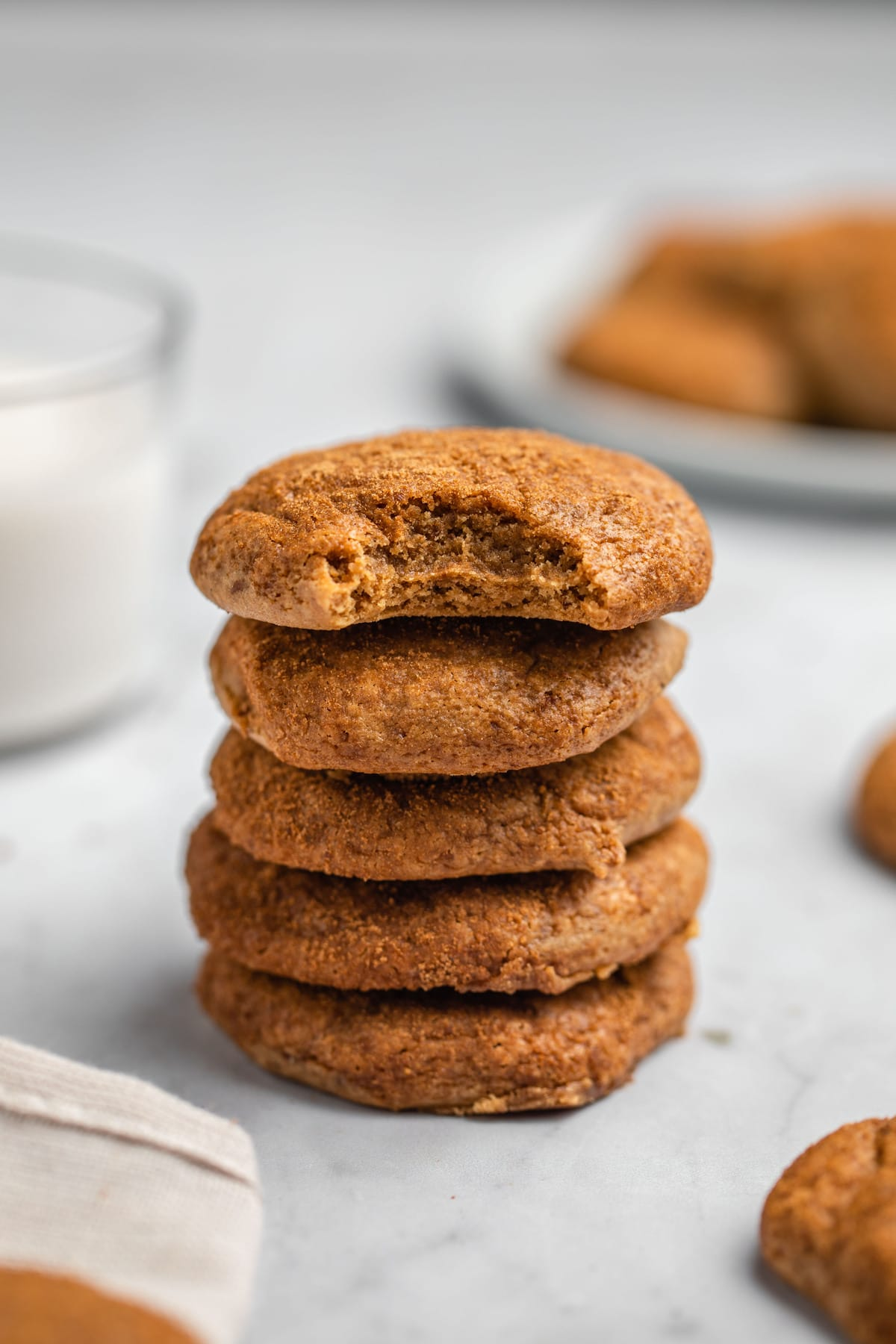stack of cashew butter snickerdoodles with bite taken out of top one on marble background