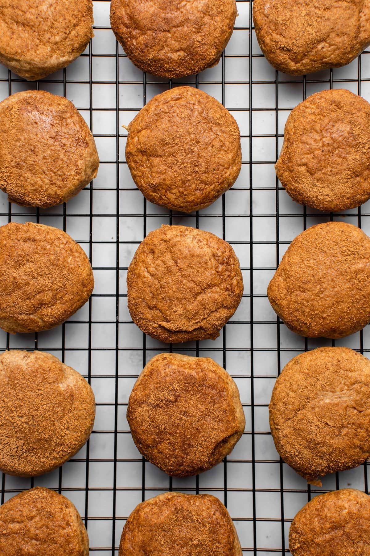 cashew butter snickerdoodle cookies cooling on black metal baking rack
