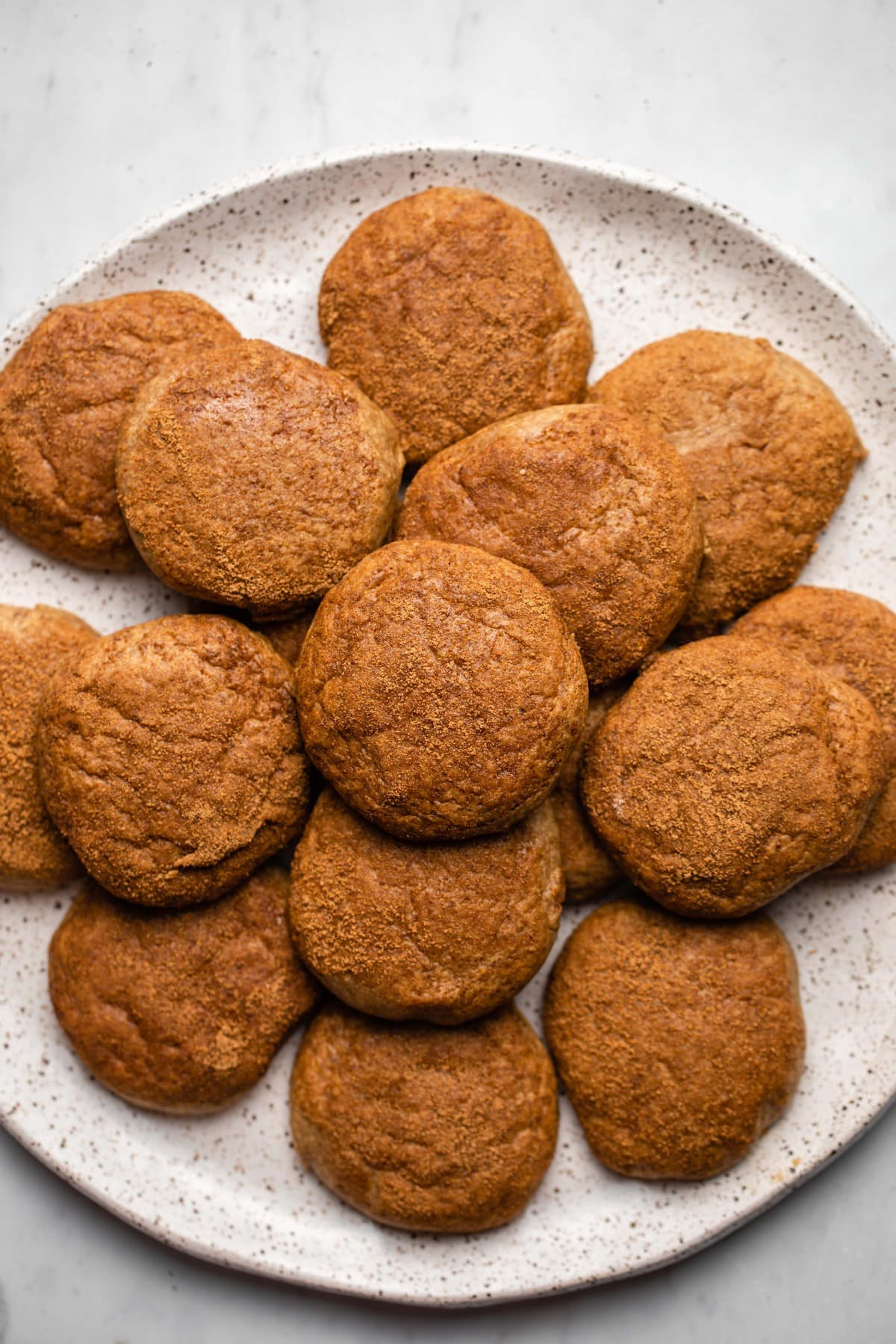 pile of snickerdoodle cookies on white speckled plate