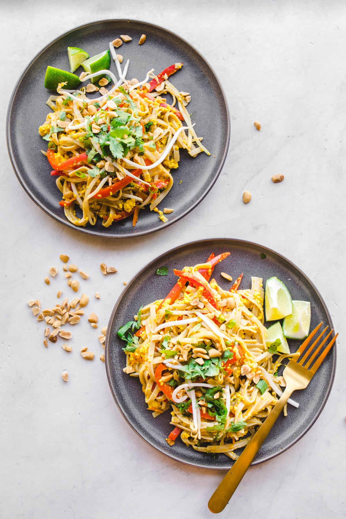 vegan pad thai with tofu and bean sprouts on grey plate