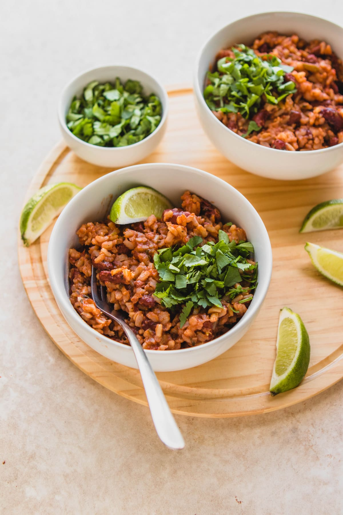 bowl of rice and beans on wood cutting board with lime
