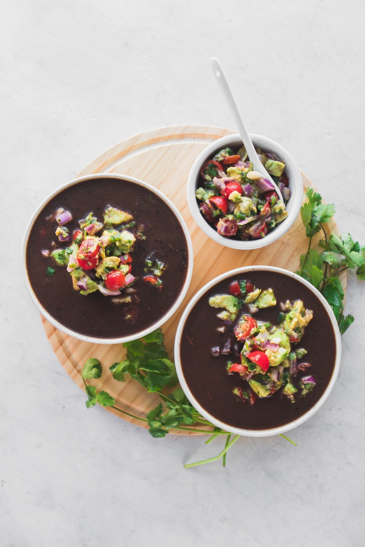black bean soup in white bowls with salsa and cilantro