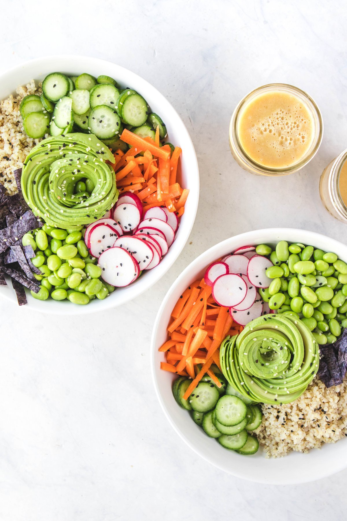 quinoa sushi bowls with jars of dressing on white background