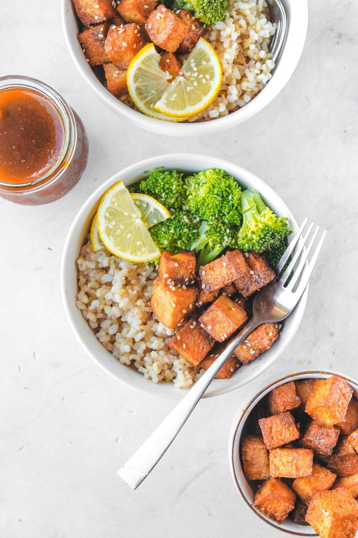 orange tofu bowls with extra tofu on the side