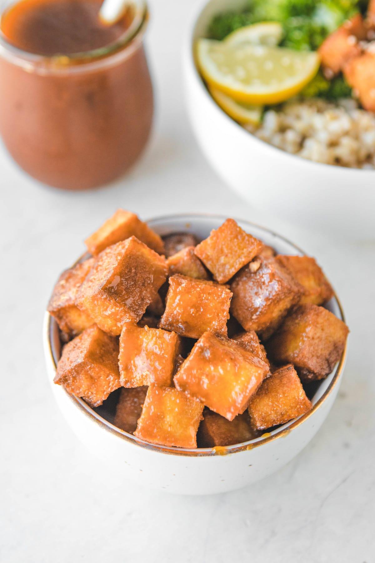 crispy orange tofu in white bowl