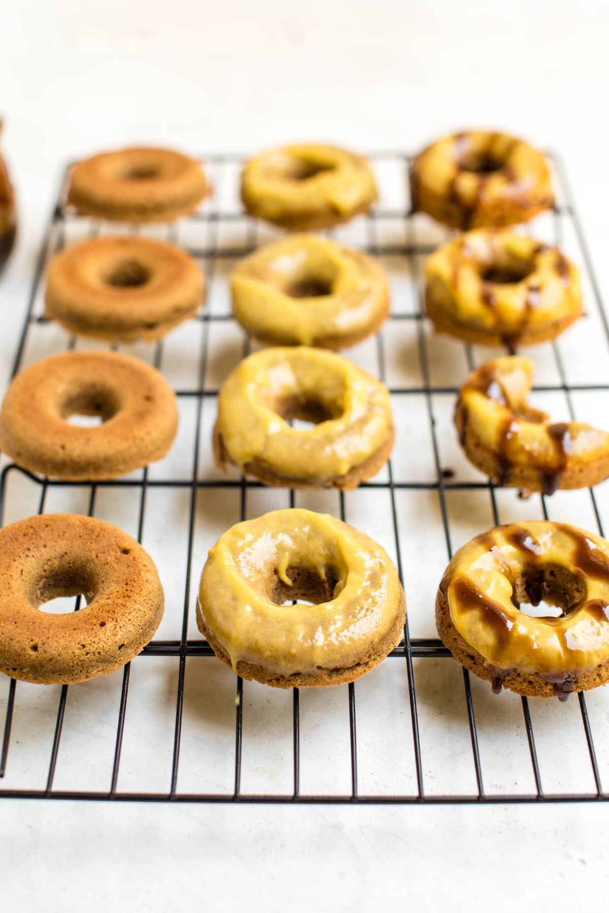 toasted coconut baked donuts on cooling rack with mango glaze