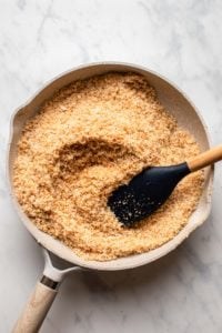 toasted coconut in nonstick pan with rubber spatula on marble background