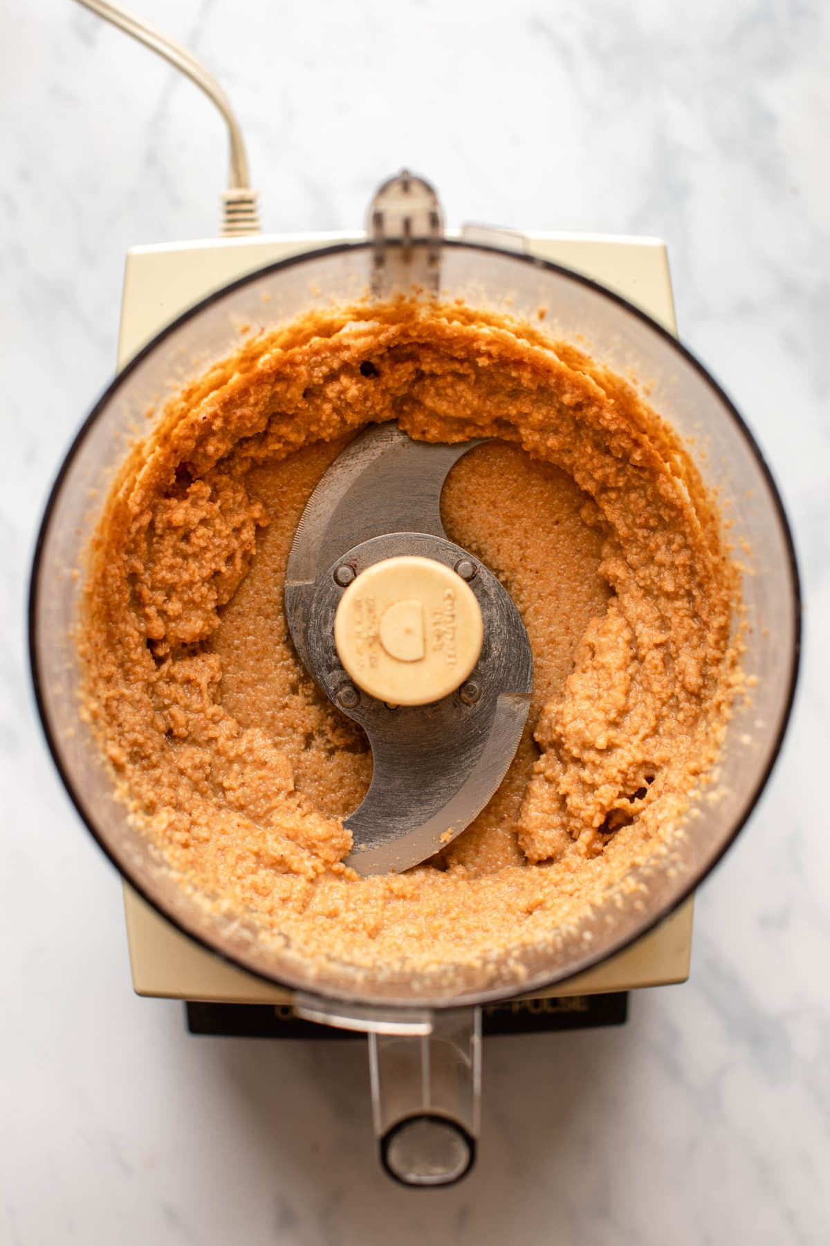 shiny and thick toasted coconut butter in food processor on marble background