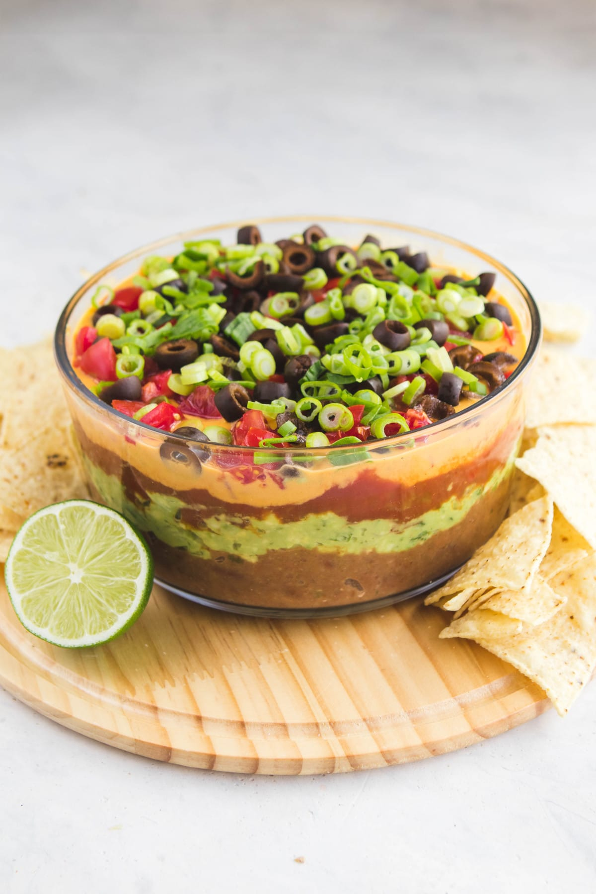 seven layer dip in glass bowl with chips