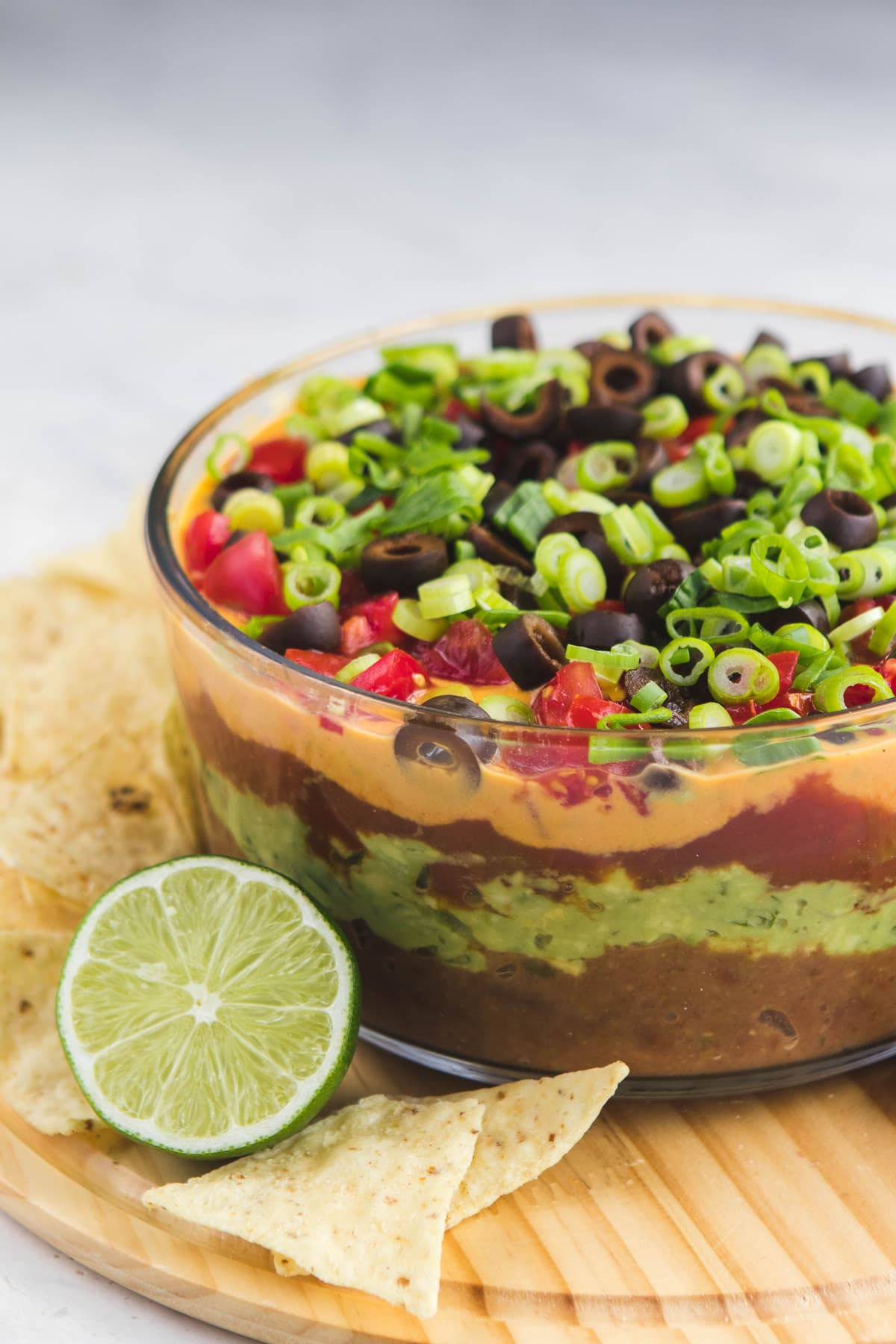 seven layer dip in glass bowl with lime