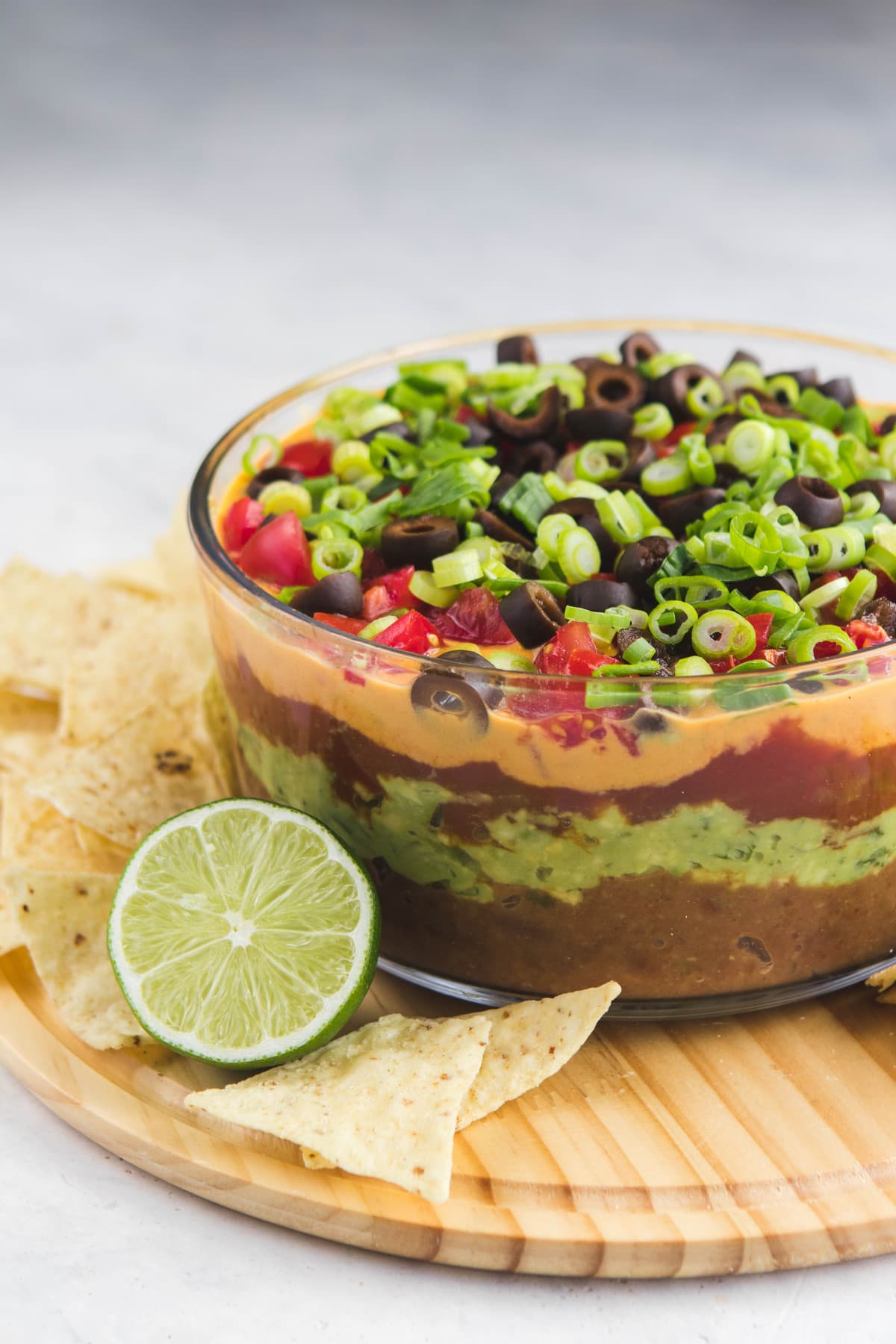 side shot of seven layer dip with lime and chips
