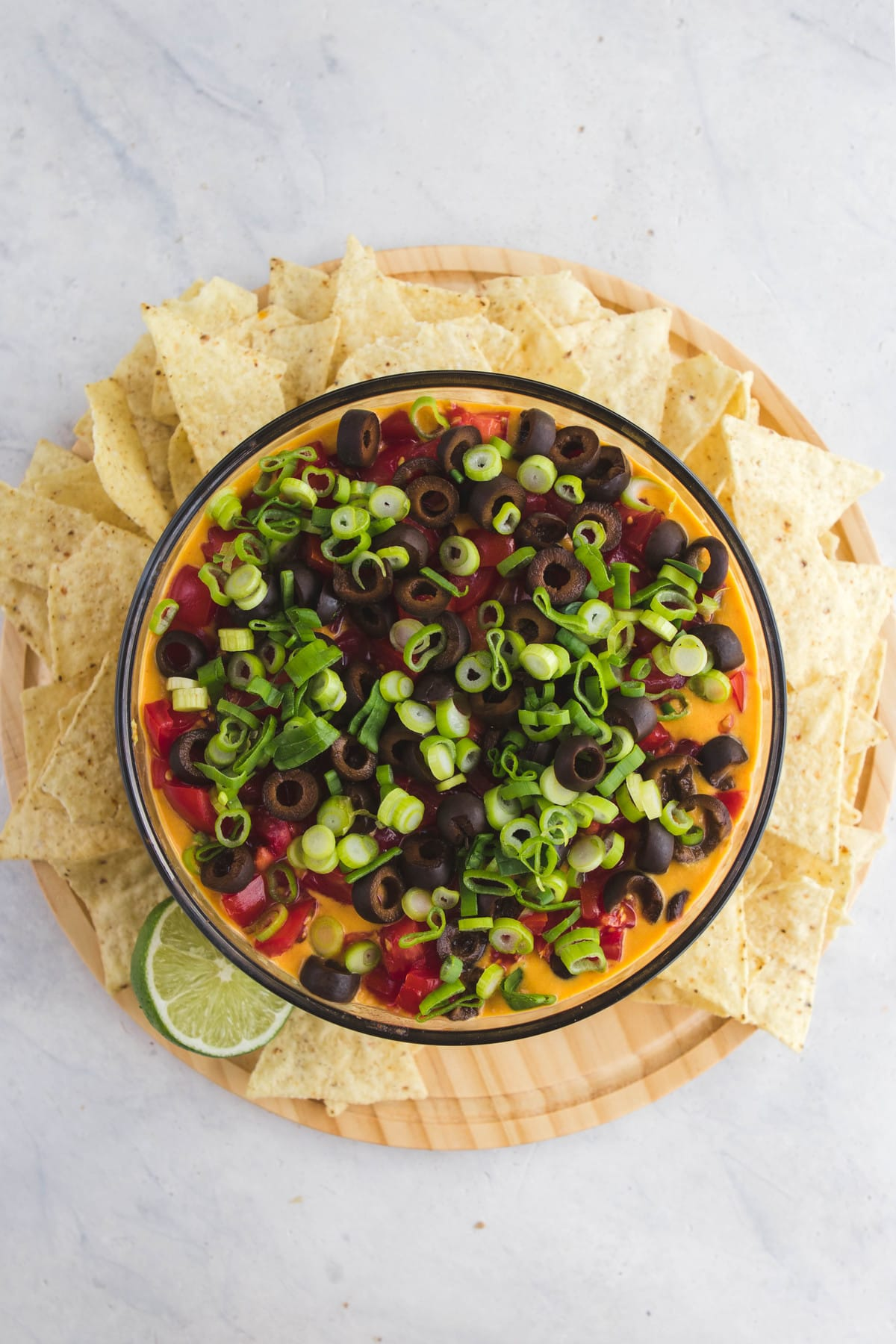 top view of seven layer dip in glass bowl with chips