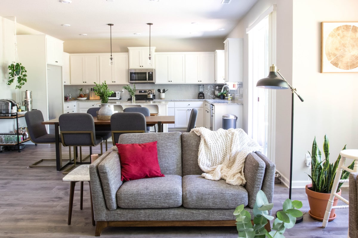 article love seat, dining room table, and white kitchen in the background