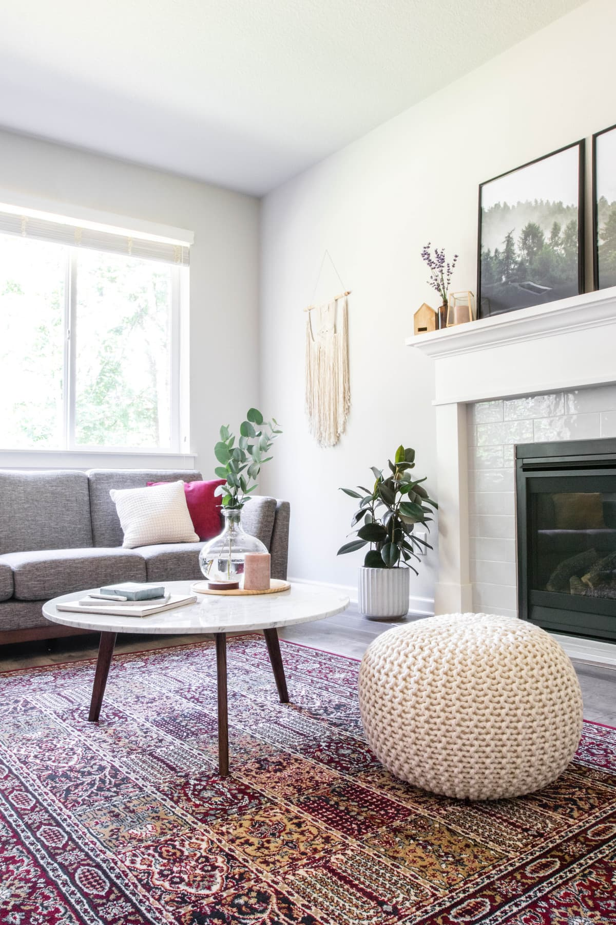 white pouf, coffee table, and couch by window
