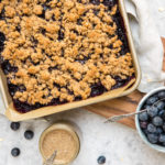 blueberry crumble bars in pan with fresh blueberries and almond butter