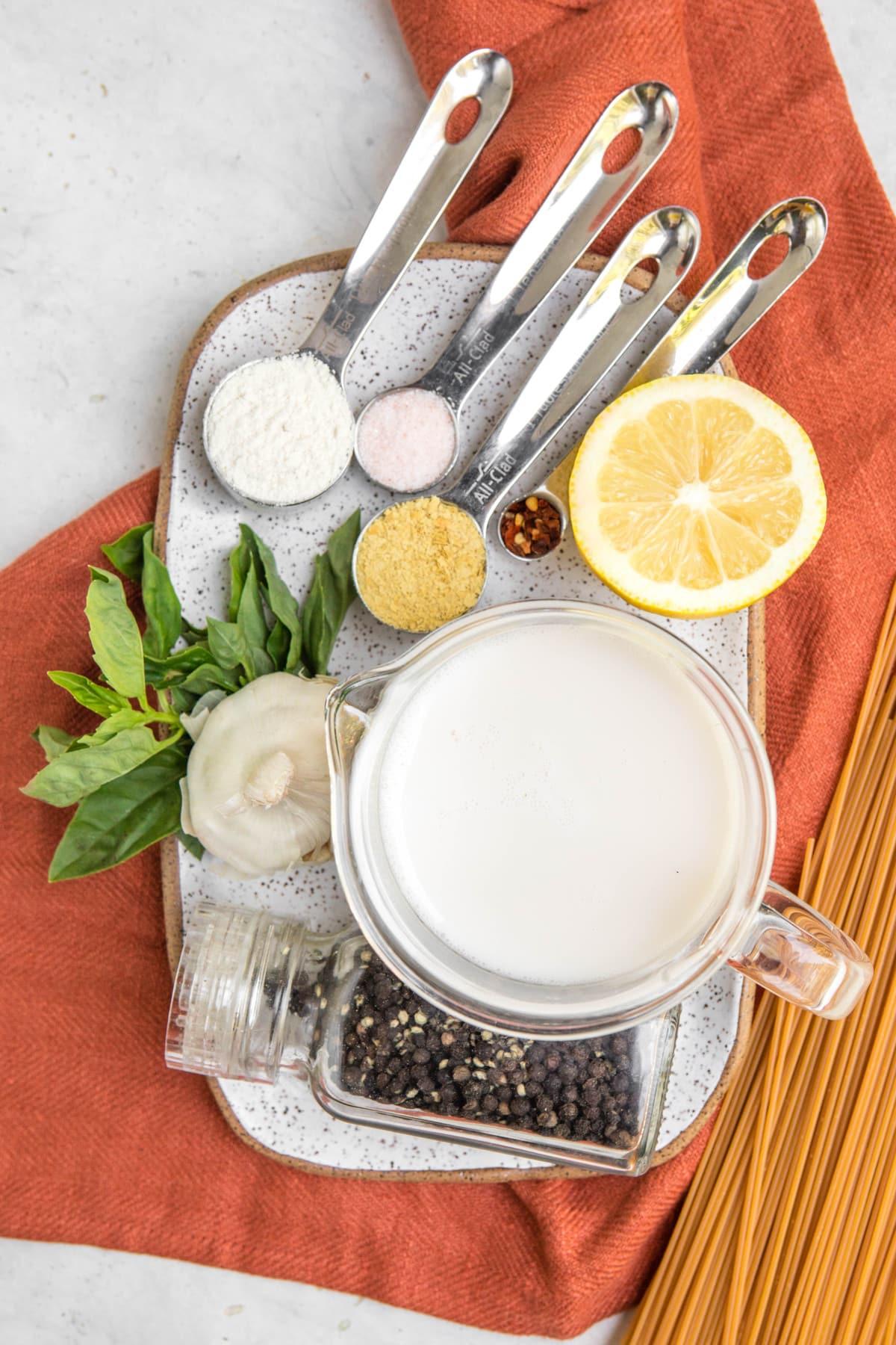 ingredients for garlic sauce pasta on white tray