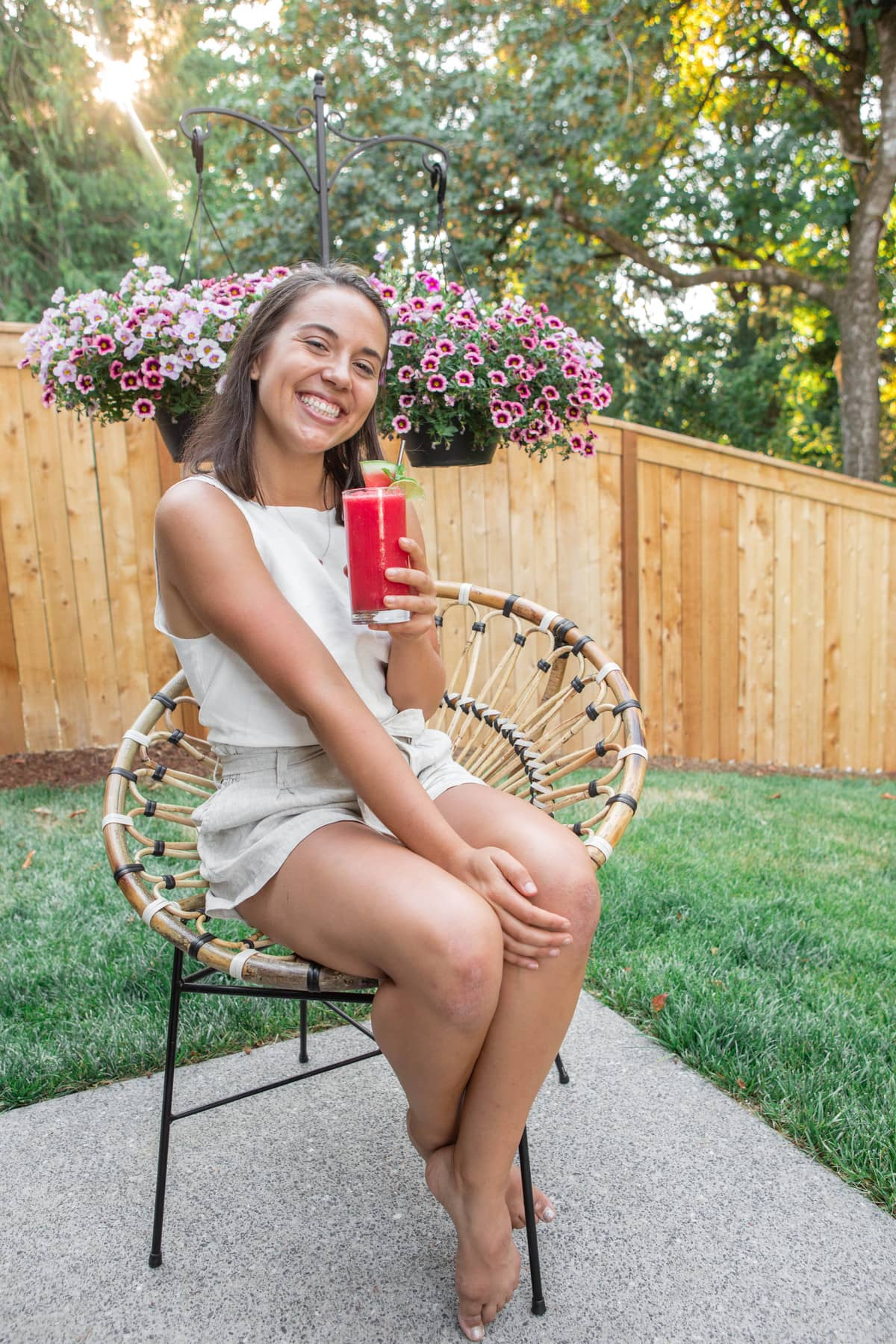 Caitlin sitting in patio chair while drinking watermelon slushie