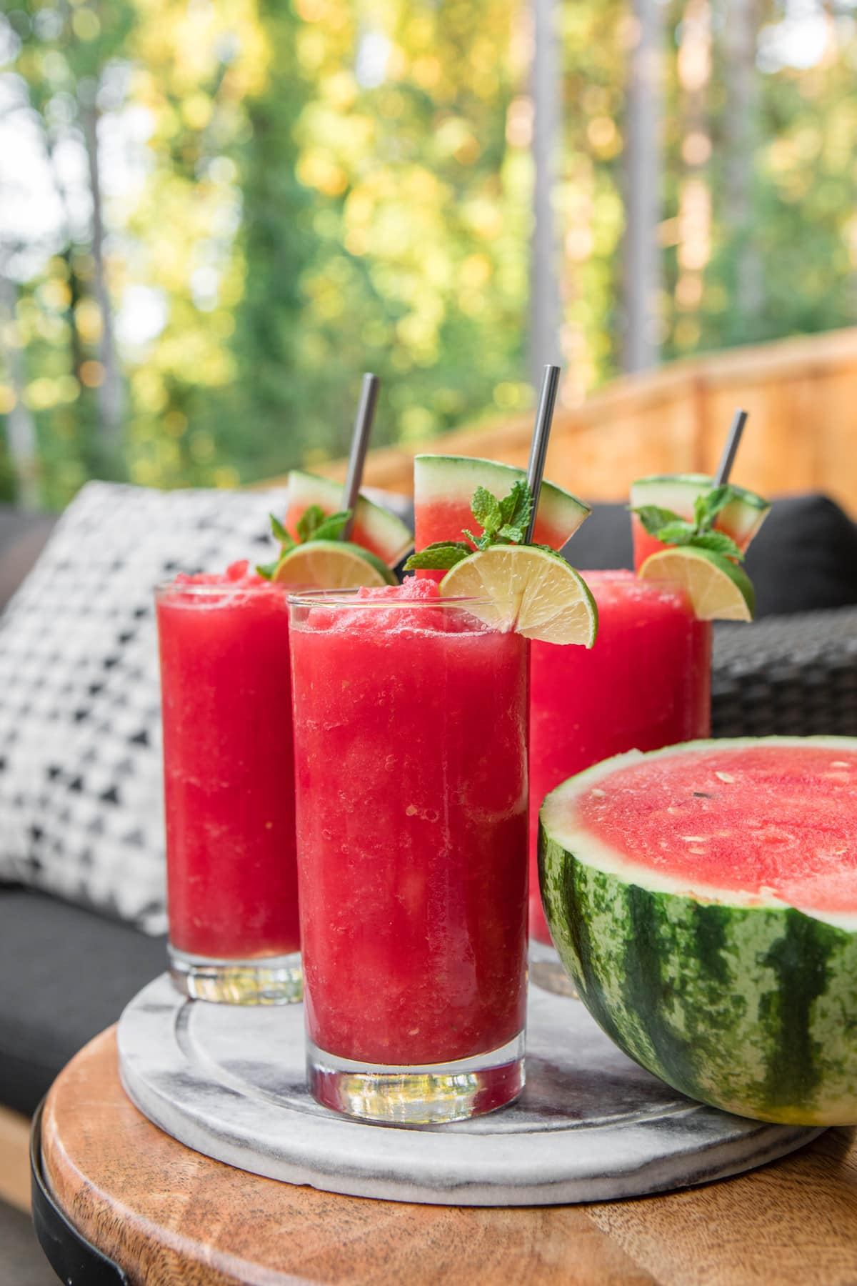 watermelon slushies in glasses with lime on patio table