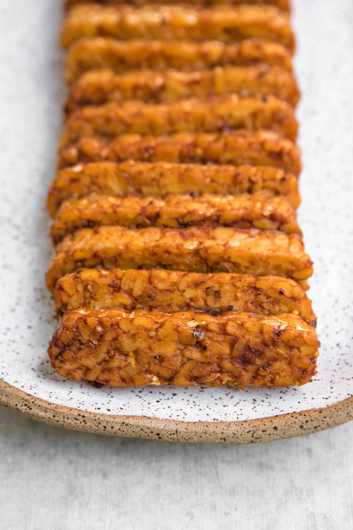 close up shot of cooked smoky tempeh on white serving platter