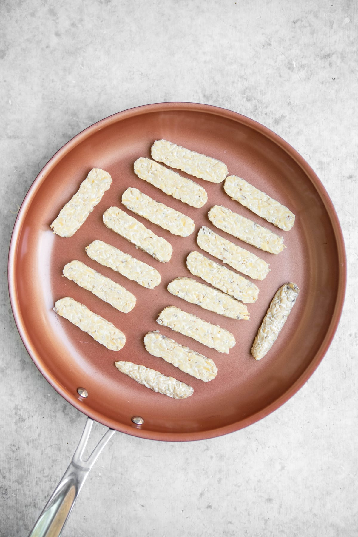 strips of tempeh lined up on nonstick pan