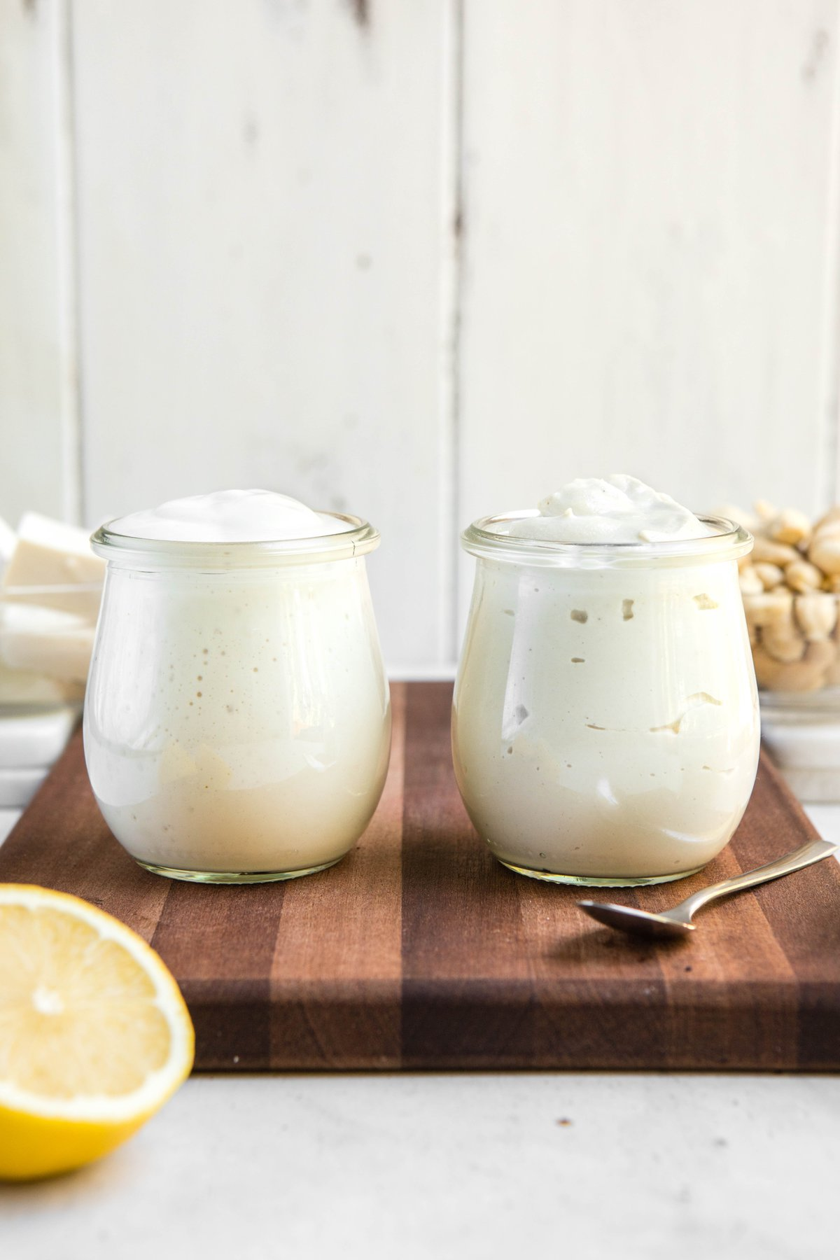 glass jars of tofu and cashew mayo on wood cutting board
