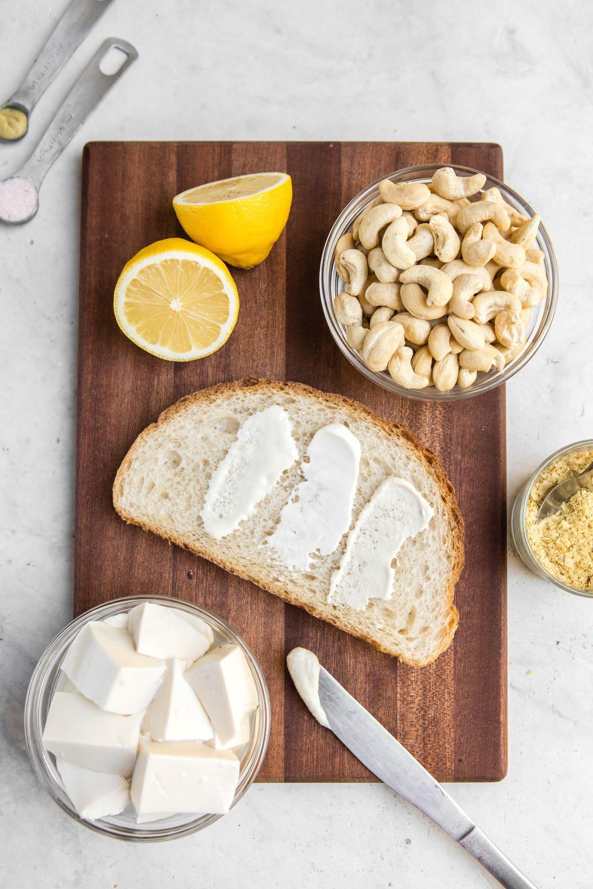jars of mayo, piece of bread, and mayo ingredients on wood cutting board