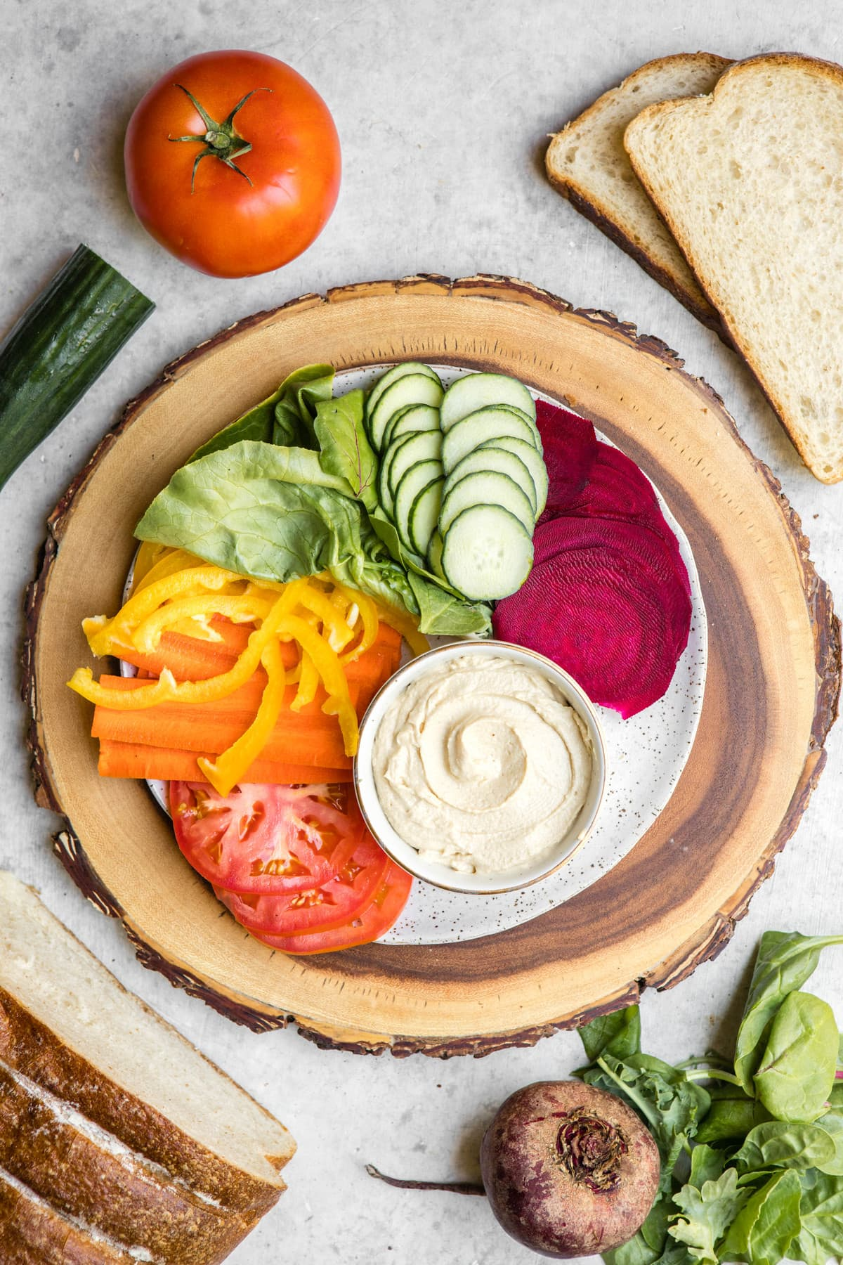 spread of rainbow vegetables, hummus, and bread on white backdrop