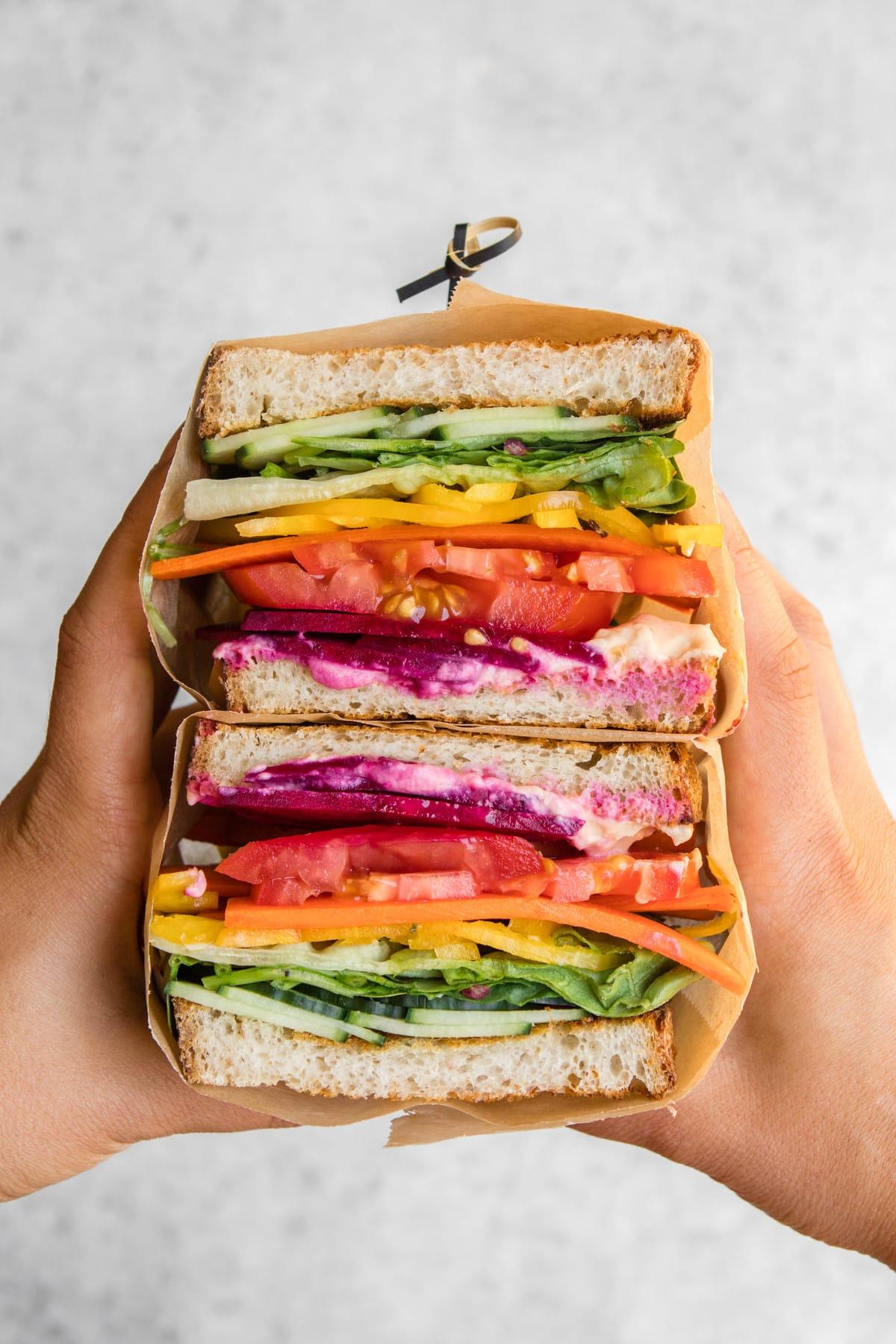 hands holding rainbow veggie sandwich cut in half
