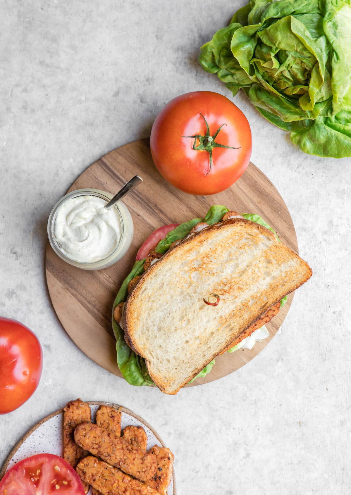 overhead photo of vegan blt on wood cutting board with tomatoes and lettuce on the side