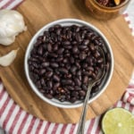 white bowl of instant pot chipotle black beans on wood background