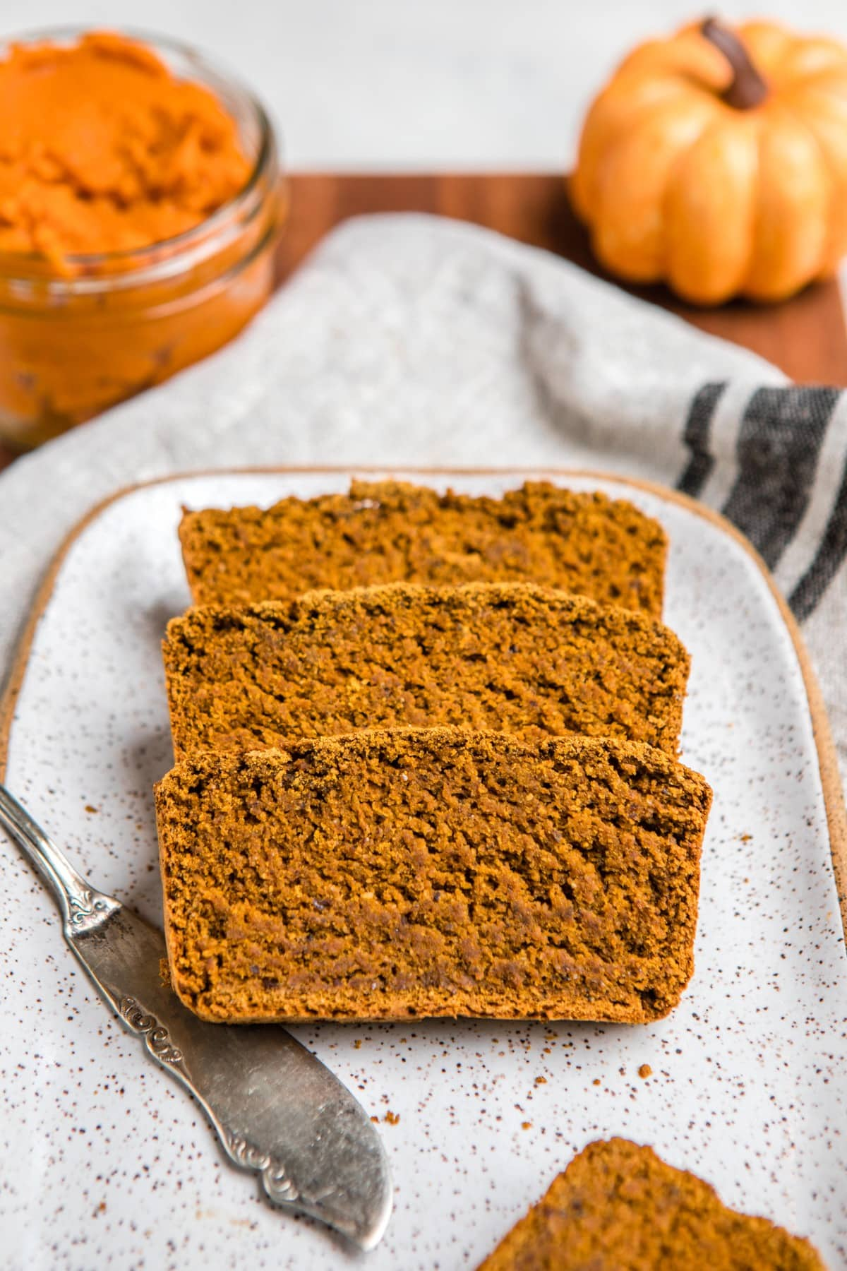 slices of vegan pumpkin bread on white serving tray