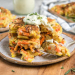 stack of root vegetable pancakes with cashew cream on wood cutting board