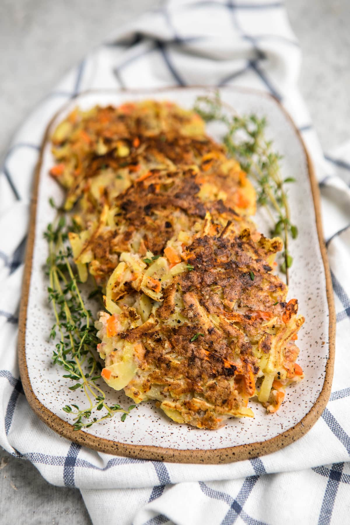 crispy root vegetable pancakes lined on white serving tray with fresh thyme