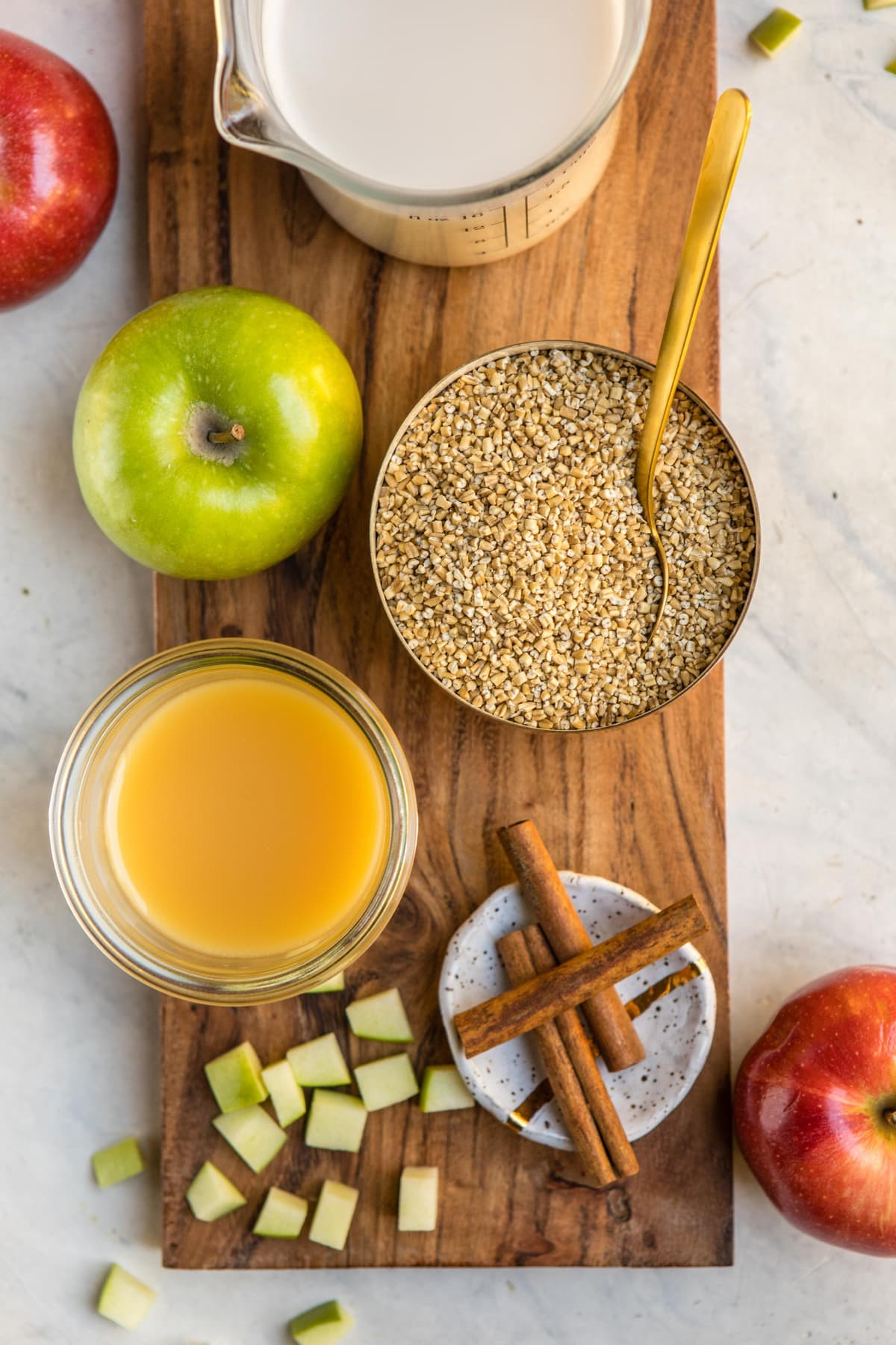 ingredients for apple cinnamon oatmeal on wood cutting board