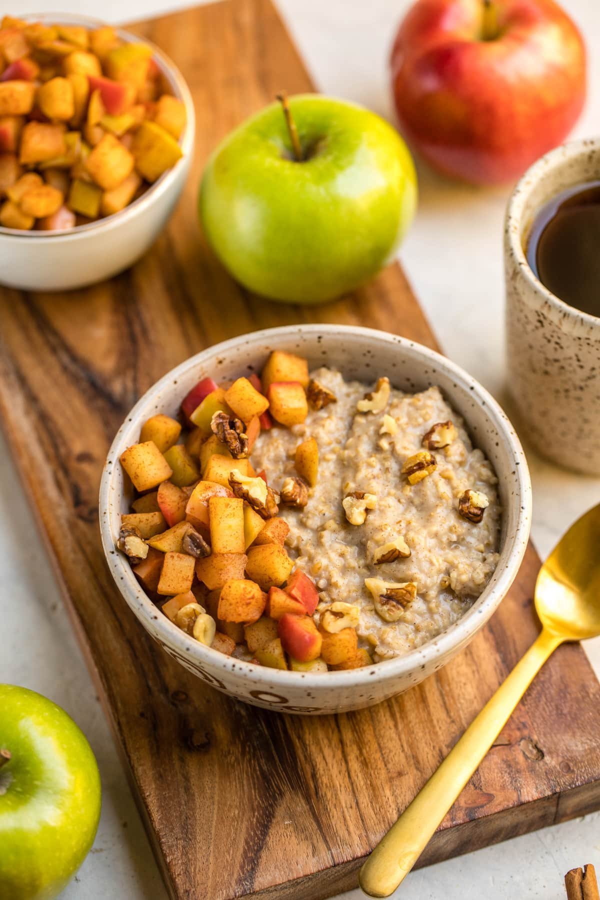 bowl of cinnamon apple oatmeal surrounded by apples on wood cutting board