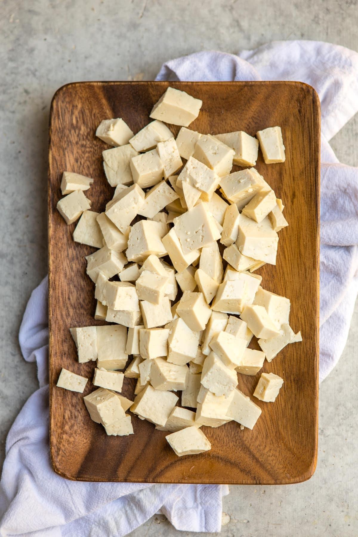 pressed and chopped medium firm tofu on wood rectangular plate