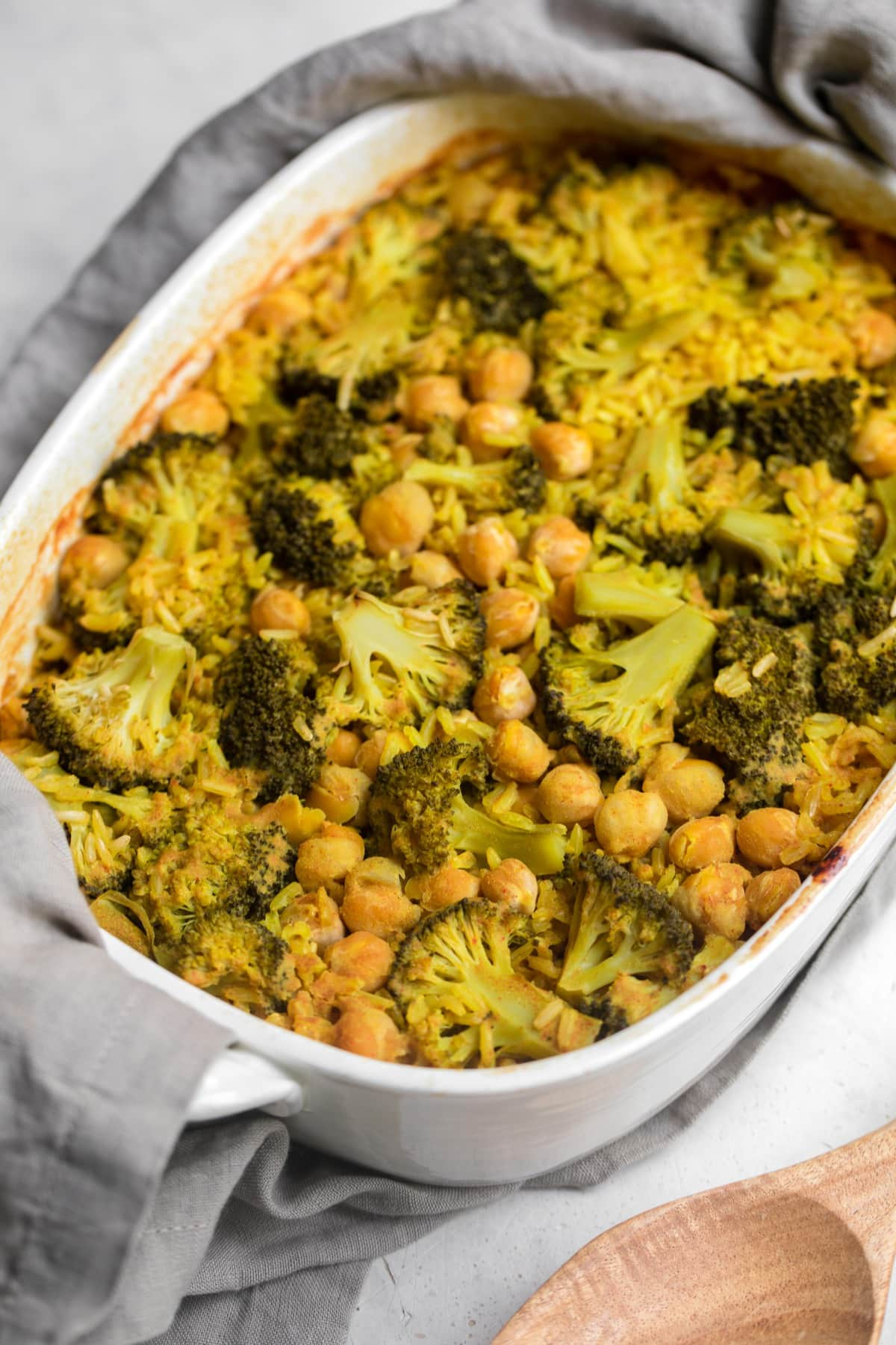 cooked broccoli rice casserole in white dish with grey towel