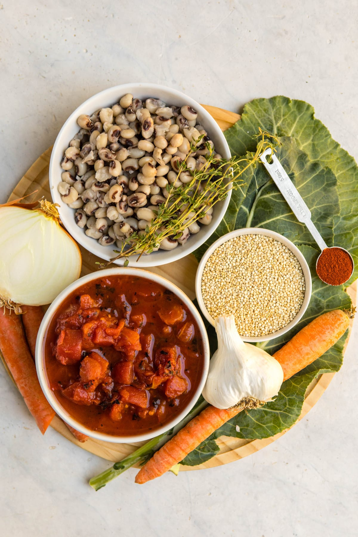 ingredients for black-eyed pea soup with quinoa on wooden cutting board