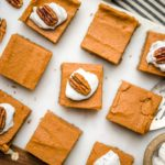 sweet potato pie bars topped with whipped cream and pecans on white marble cutting board