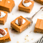 sweet potato pie bars topped with coco whip and a pecan on white serving tray