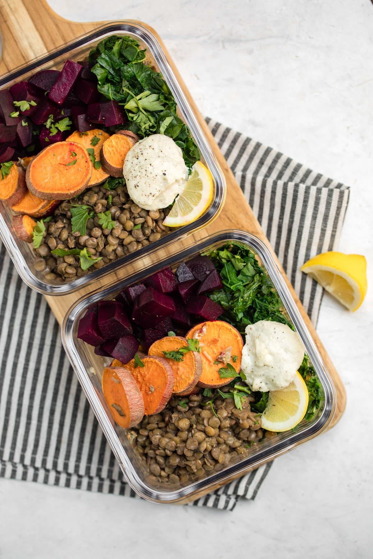 glass tupperwares filled with warm lentil salad ingredients for meal prep