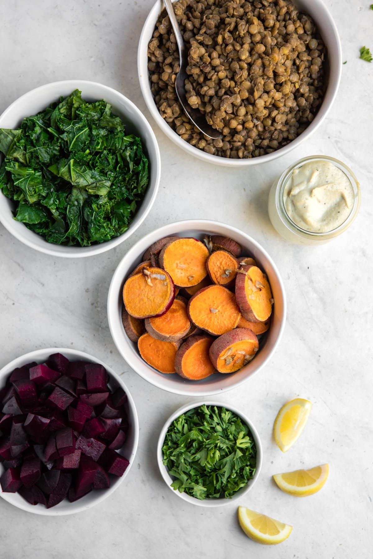 ingredients for warm lentil salad with roasted vegetables in white bowls on white marble background